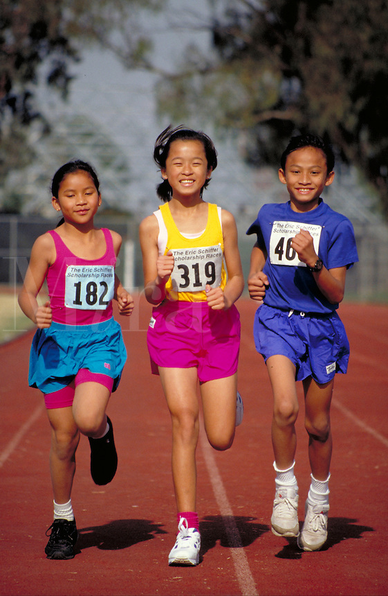 CAMBODIAN-AMERICAN PRIZE-WINNING ATHLETES RUNNING TOGETHER ON TRACK. CAMBODIAN-AMERICAN ATHLETES. LONG BEACH CALIFORNIA.