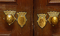 Detail of the polished brass door knobs and keyholes of a double door at Petworth House