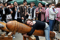 A tourist hugs a metal penis at the penis festival in Kawasai. During the festival a huge pink penis is carried through the streets of Kawasaki at the Kanamara Matsuri (Festival of the Steel Phallus) 05 April 2009.   The shinto festival dating back to the edo period350 years ago, has it's roots where prostitutes prayed not only that business would be brisk, but for protection from syphilis.  With the spread of syphilis now curbed, participants in the modern festival solicit donations for HIV/AIDS research.