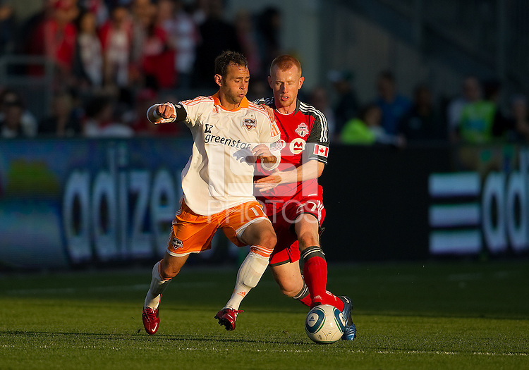 07 May2011: Houston Dynamo midfielder Brad Davis #11and Toronto FC defender Richard Eckersley #27 in action during an MLS game between the Houston Dynamo and the Toronto FC at BMO Field in Toronto, Ontario.