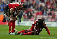 Jason Denayer of Sunderland (R) is injured on the ground being spoken to by team mate John O'Shea  during the Premier League match between Sunderland and Swansea City at the Stadium of Light, Sunderland, England, UK. Saturday 13 May 2017