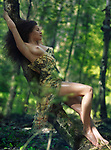Sensual erotic portrait of a beautiful sexy half nude woman in a wet sheer summer dress revealing her naked breast and legs leaning against a tree trunk in the nature with dreamy romantic expression