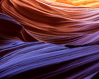 Reflected light creates rich color and deep hues to the winding sandstone in a remote slot canyon of Arizona.