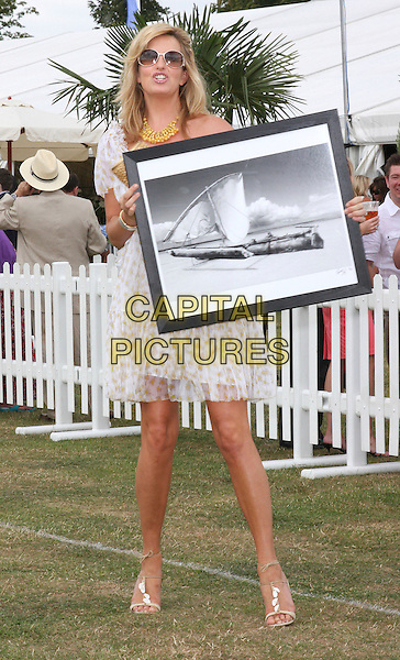 PENNY LANCASTER STEWART .Duke Of Essex Polo Trophy at Gaynes Park, Epping, Essex, England, UK,.July 4th 2009..full length white sheer puff sleeve off the shoulder dress blouson strappy sandals holding picture print.CAP/ROS.©Steve Ross/Capital Pictures