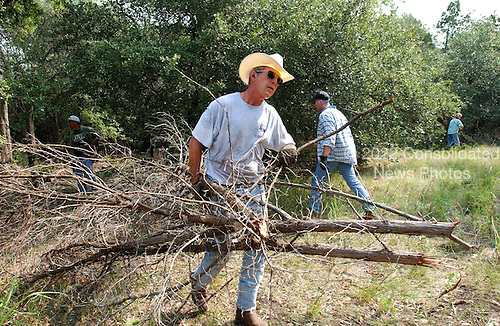 United States President George W. Bush clears cedar at his ranch in Crawford, Texas, Friday, August 9, 2002. <br /> Mandatory Credit: Eric Draper - White House via CNP