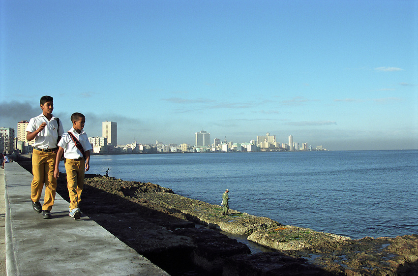 Two boys in school uniforms walking along the breakwater of Havana Harbor, against the back-drop of the city skyline, passing by fishermen on the shore.