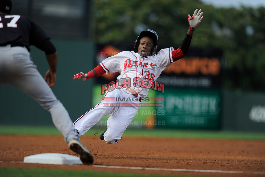 Shortstop Jose Vinicio (36) of the Greenville Drive slides into third base with a first-inning triple in a game against the Kannapolis Intimidators on Monday, August 5, 2013, at Fluor Field at the West End in Greenville, South Carolina. Kannapolis won, 3-0. (Tom Priddy/Four Seam Images)