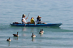 Women  & dog kayaking Lake Tahoe near canada geese