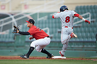 Justin Yurchak (33) of the Kannapolis Intimidators waits for the throw as Josh Stephen (8) of the Lakewood BlueClaws lunges for first base at Kannapolis Intimidators Stadium on April 6, 2018 in Kannapolis, North Carolina.  The BlueClaws defeated the Intimidators 4-3. (Brian Westerholt/Four Seam Images)