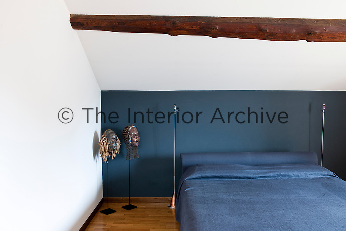 An attic bedroom with a sloping roof and a feature wall painted blue with bedlinens of the same color