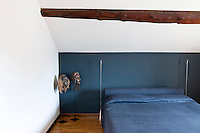 An attic bedroom with a sloping roof and a feature wall painted blue with bed linens of the same color