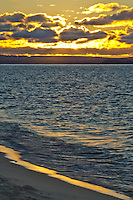Sand Point Beach is under a golden glow at sunset as the sun sets into Lake Superior, Pictured Rocks National Lakeshore, Alger County, Michigan
