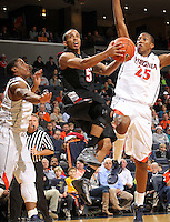 Dec. 22, 2010; Charlottesville, VA, USA; Seattle Redhawks guard Cervante Burrell (5) shoots between Virginia Cavaliers guard Jontel Evans (1) and Virginia Cavaliers forward Akil Mitchell (25) during the game at the John Paul Jones Arena. Mandatory Credit: Andrew Shurtleff