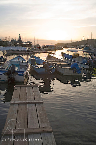 A sunset at the Marina, fishing boats (pirogues), jetty, lighthouse