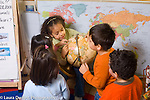 Preschool 3-4 year olds group of children interested in globe looking at it and pointing at countries horizontal