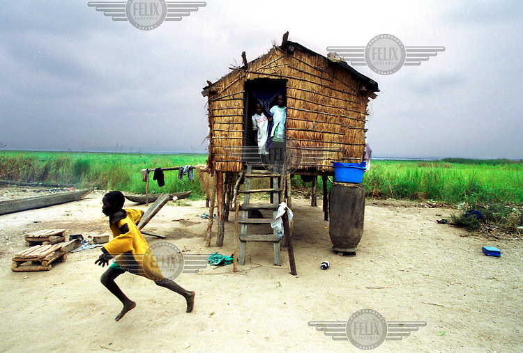 ©Sven Torfinn/Panos Pictures..Democratic Republic of the Congo (DRC), village on one of the many small islands in the Congo river near the capital Kinshasa, june 2001.The people on this islands live in buildings on stilts because of the high water level during rainy season.Boy is running away..All tough the population is informed about the importance of the vaccination against polio, they are still afraid and suspicious when the vaccination team is visiting them.