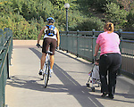 Caucasian female biker passing an Hispanic mother pushing a baby stroller, Denver, Colorado. .  John offers private photo tours in Denver, Boulder and throughout Colorado. Year-round Colorado photo tours. .  John offers private photo tours in Denver, Boulder and throughout Colorado. Year-round.