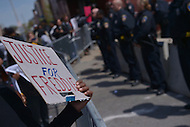 Baltimore, MD - April 25, 2015: A woman holds a sign as hundreds of protestors gathered near the Baltimore Police Department's Western District Headquarters April 25, 2015 to demand police accountability in the death of Freddie Gray and protest police brutality. Gray died of a broken spine while in police custody.  (Photo by Don Baxter/Media Images International)