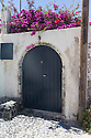 Santorini, Greece. 06.05.2014. Gate, with bougainvillea above, in the whitewashed, mediaeval, village of Finikia. The homes in this village have been constructed in the hyposcafa manner i.e. the lower portions are dug out from the ground. Photogaph © Jane Hobson.