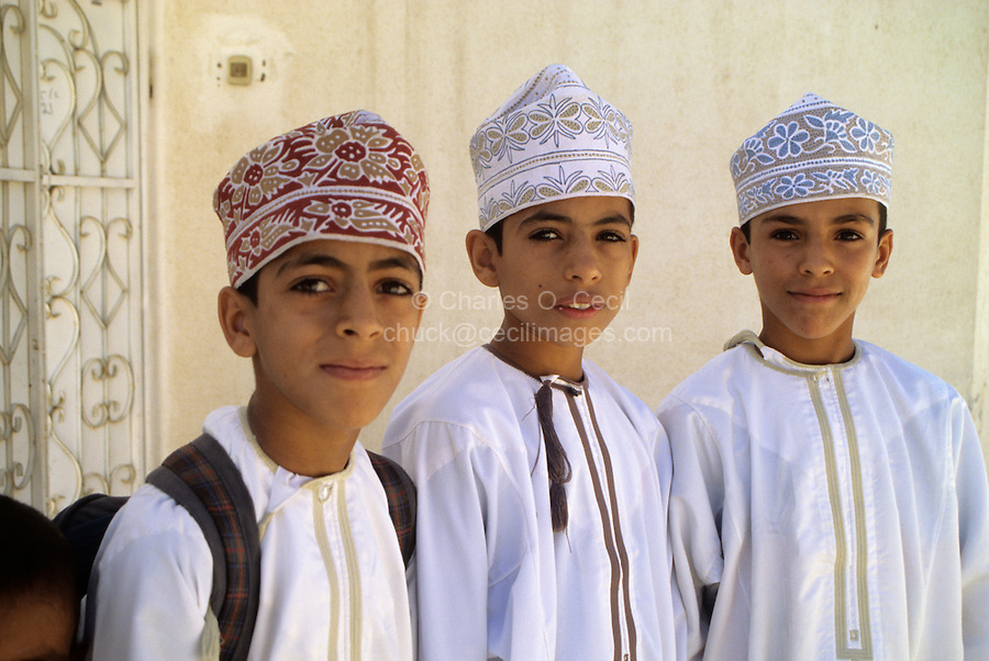 Wadi Bani Kharus, Oman, Arabian Peninsula, Middle East - Omani Schoolboys wearing the traditional embroidered Omani cap, the kummah, and traditional robe, the dishdasha.   A tassel several inches long, called a kashkusha or a frakha, hangs from the right side of the neckline of each dishdasha.  The kashkusha is often perfumed.