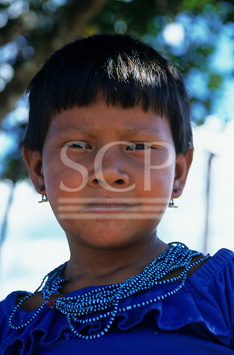 Koatinemo village, Brazil. Young Assurini Indian girl in blue dress with blue bead necklace and earrings
