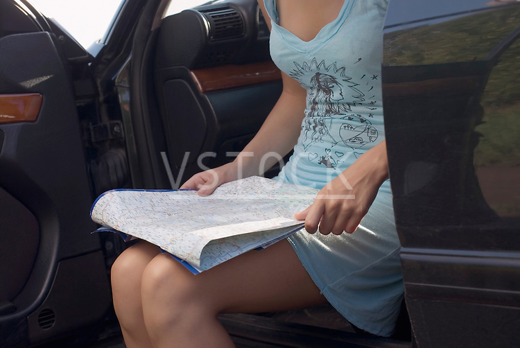 Young woman sitting in car and reading map, mid section