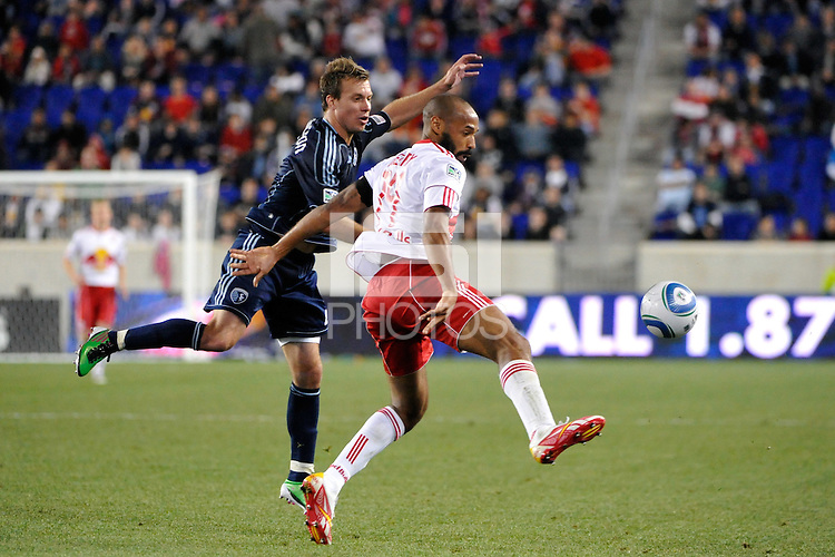 Thierry Henry (14) of the New York Red Bulls p[lays the ball under pressure from Michael Harrington (2) of Sporting Kansas City. The New York Red Bulls defeated Sporting Kansas City 1-0 during a Major League Soccer (MLS) match at Red Bull Arena in Harrison, NJ, on April 30, 2011.
