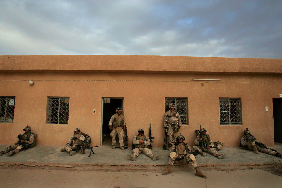 US Marines with Fox Co. 2nd Battalion 1st Marines relax after moving into what will be home for the night - a drafty abandoned concrete floored school - at the end of the third day of Operation Steel Curtain, an operation to clear Husaybah (a city on the Iraq-Syrian border) of insurgents on Tues. Nov. 7, 2005.