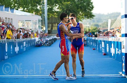 25 JUN 2011 - PONTEVEDRA, ESP - Javier Gomez (ESP) (right) thanks Ivan Rana (ESP) for his support on the run at the Elite Men's European Triathlon Championships in Pontevedra, Spain .(PHOTO (C) NIGEL FARROW)