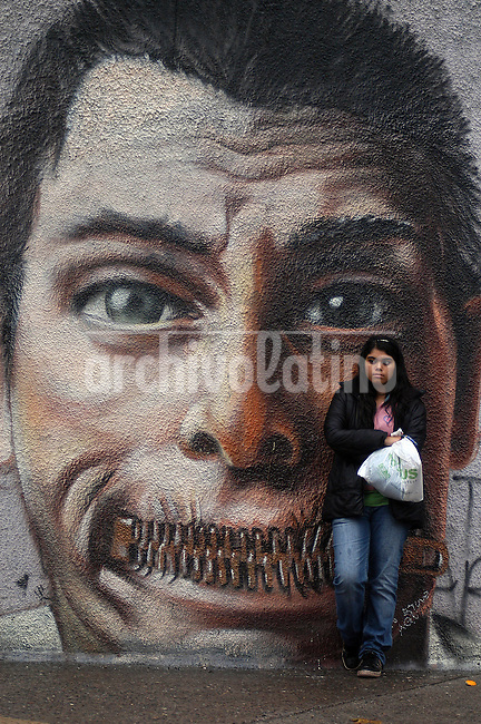 A young Chilean girls stands near a graffitti representing lack of freedom.