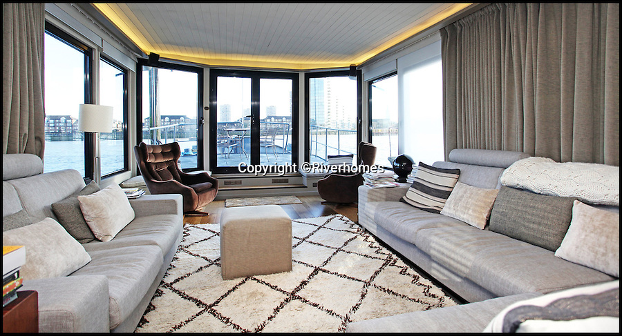BNPS.co.uk (01202 558833)<br /> Pic: Riverhomes/BNPS<br /> <br /> Luxury lounge.<br /> <br /> Heart of Lightness - Tardis like houseboat on the Thames.<br /> <br /> A houseboat that looks more like a luxurious penthouse suite inside has gone on the market for a whopping £1.5 million - because it's in one of London's most exclusive locations.<br /> <br /> The 100ft vessel was once a former Dutch barge taking supplies up and down the Thames until it was retired from service in the 1960s and left to rot.<br /> <br /> But a decade later it was salvaged and turned into a houseboat before undergoing a complete refurbishment four years ago and moved to a premier mooring alongside one the swankiest addresses in the city.<br /> <br /> The plush houseboat, berthed at the entrance to Cheyne Walk, now boasts a lavish living room, stylish 50ft-long kitchen, a spiral staircase, two opulent bedrooms, three bathrooms and even a sun terrace.<br /> <br /> And despite its eye-watering £1.5m asking price, experts at Riverhomes estate agents say the houseboat is actually a bargain and that anyone wanting to live in such luxury in the heart of Chelsea would have to shell out many millions more.
