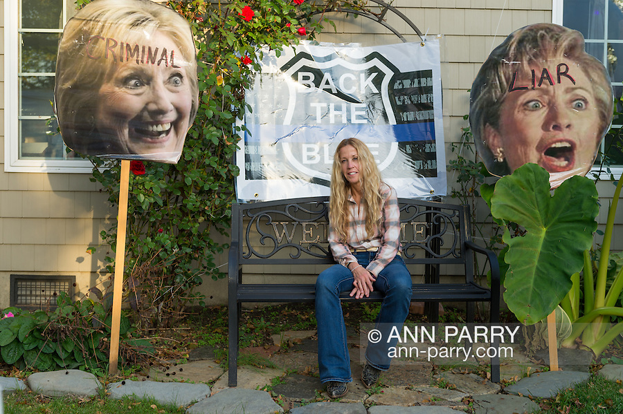 """Bellmore, New York, USA. November 2, 2016. EILEEN FUSCALDO, a Donald Trump Supporter, sits in her front yard on a bench seat with large pictures of Hillary Clinton's head on sticks, and """"Back the Blue"""" police badge sign behind her, some of many in her front yard Halloween display for the Republican presidential candidate, D. J. Trump, and against Democratic one, H. R. Clinton."""