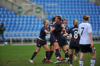 Carli Lloyd is congratulated by Abby Wambach (R), and Heather Mitts (L) and the rest of the team after scoring a goal.  The USA captured the 2010 Algarve Cup title by defeating Germany 3-2, at Estadio Algarve on March 3, 2010.