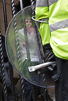 Pro EDL Demonstrator, cordoned or kettled by main entrance of Bennetts Bar, gazing out through a police riot shield. Bennetts Hill, Birmingham City Centre Birmingham, 5th Sept 2009
