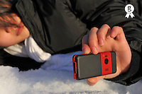 Girl lying on snow, taking photo with cellphone (Licence this image exclusively with Getty: http://www.gettyimages.com/detail/93522417 )