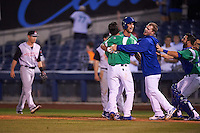 Tulsa Drillers pinch hitter Chase De Jong (34) is mobbed by teammates including Brandon Trinkwon (8), Alex Verdugo (hoodie) and catcher Tyler Ogle after a walk off bunt due to an error during a game against the Arkansas Travelers on April 28, 2016 at ONEOK Field in Tulsa, Oklahoma.  Tulsa defeated Arkansas 5-4.  (Mike Janes/Four Seam Images)