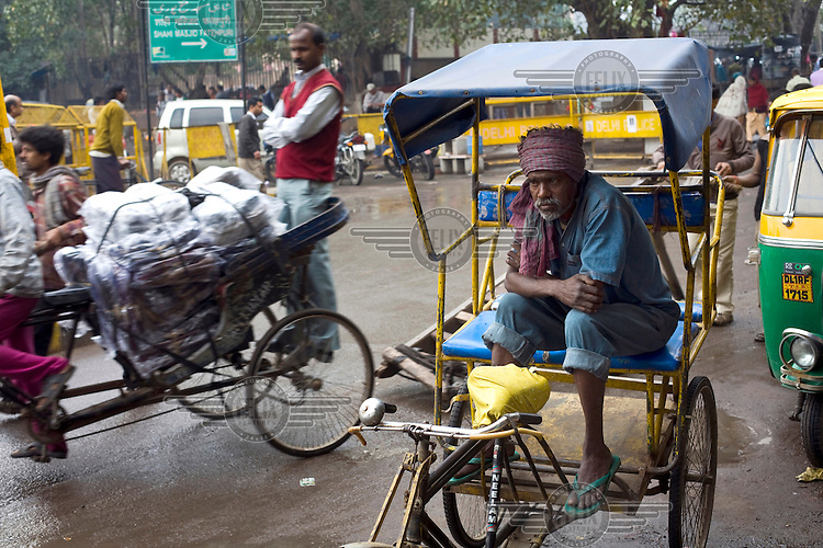 40 year old Ravi Hazara, a rickshaw puller in Old Delhi waiting for a job outside a motor part shop that often employs him.
