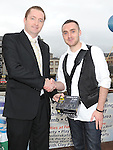 Jason McCarthy winner of the over 18 section of the RTE Local Heroes photo competition receives his prize from Tadhg Leonard representing sponsors Nikon and mahers chemist. Photo: Colin Bell/pressphotos.ie