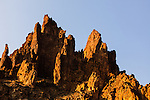 The spires of volcanic tuff in Leslie Gulch point toward a clear blue sky in the arid Southeast Oregon region.
