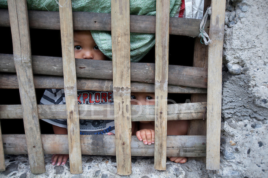 Two young children look through bamboo bars on a window in their house in a rural area near the Twin Lakes National Park on Negros Island, Philippines.