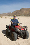 Man riding a Quad in the arroyo near Migrino, Baja California, Mexico