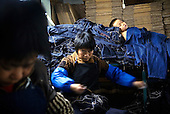 """Workers sew jeans in Mr Huang's factory in Zhongshan city, China, while a child sleeps on a pile of jeans. .This picture is part of a photo and text story on blue jeans production in China by Justin Jin. .China, the """"factory of the world"""", is now also the major producer for blue jeans. To meet production demand, thousands of workers sweat through the night scrubbing, spraying and tearing trousers to create their rugged look. .At dawn, workers bundle the garment off to another factory for packaging and shipping around the world..The workers are among the 200 million migrant labourers criss-crossing China.looking for a better life, at the same time building their country into a.mighty industrial power."""