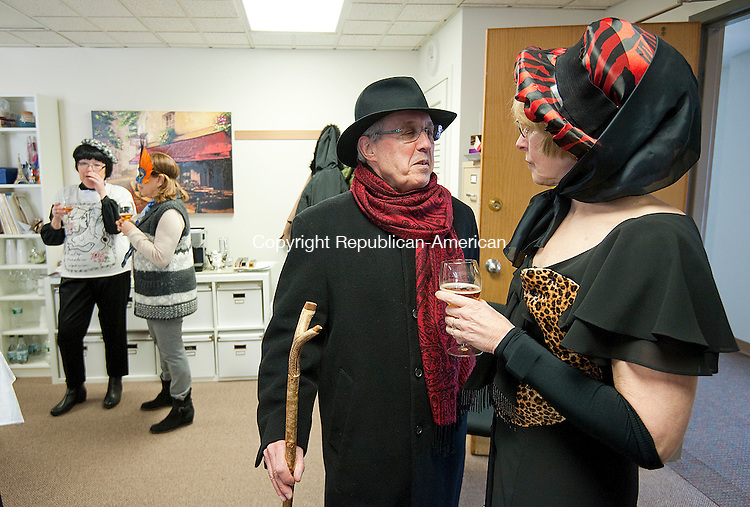 SOUTHBURY, CT--- -020716JS07--Jean-Marie Gutierrez, left, and his wife Marda Gutierrez, both of Southbury, enjoy some French cider during a Arty Gras Party to celebrate Mardi Gras at the office of Alliance Francaise of Northwest Connecticut in Southbury on Sunday. Guests were encouraged to dress up as a famous painter or painting. Jean-Marie is dressed as Aristide Bruant, a French cabaret singer, depicted on posters by posters by Henri de Toulouse-Lautrec, while Marda is dressed as Jane Avril, a dance also depicted by Toulouse-Lautrec. Jim Shannon Republican-American