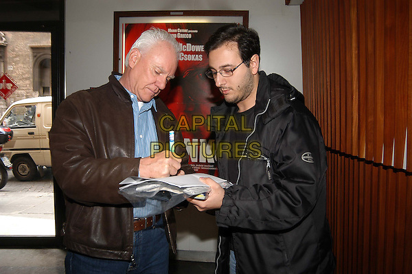 "MALCOLM MCDOWELL.Photocall for film ""Evilenko""Fontane Cinema, Rome, Italy     .May 11th, 2004               .half length, half-length, brown leather jacket, fan, signing autographs.www.capitalpictures.com.sales@capitalpictures.com.© Capital Pictures."