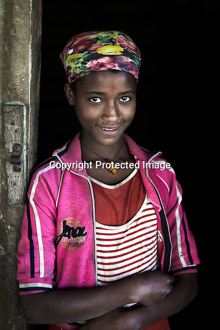 BONGA, ETHIOPIA:  Portraits of daughter of a coffee sorting worker woman who works at Kaffa Forest Coffee Farmers' Cooperative Union on December 10, 2012 outside Bonga, Ethiopia. This Kaffa region is known for its coffee production, wild coffee grown in high altitudes. This region is the original home of the coffee plant, coffee Arabica which grows in the forest of the highlands. The red berries are the main source of income in the area. Children and cattle also drink coffee. (Photo by: Per-Anders Pettersson)