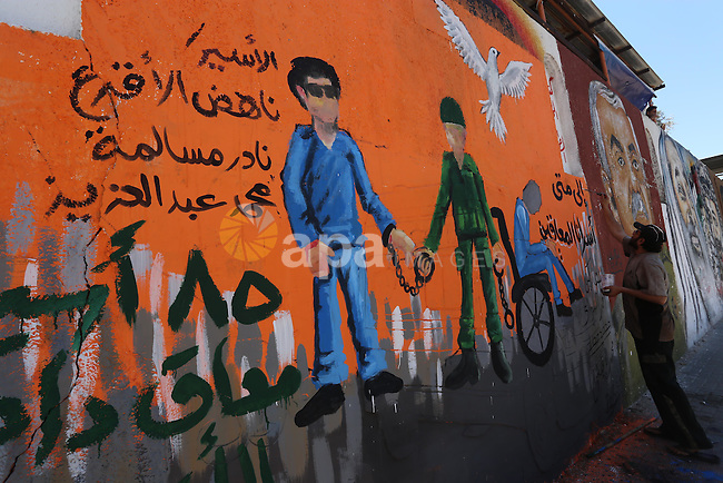 A Palestinian artist paints a mural on a wall during a rally to show solidarity with disabled prisoners, in Israeli jails, in Gaza city, on May 4, 2015. Photo by Mohammed Asad