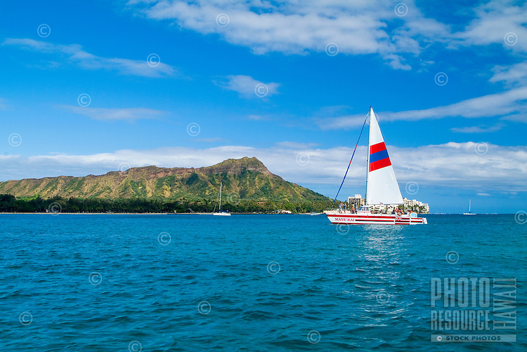 Long shot of Diamond Head from a sailboat off Waikiki with a catamaran sporting a white striped sail in the foreground.