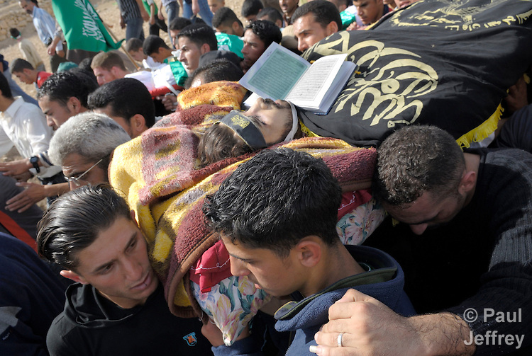 The body of Thear Hasan, a Palestinian killed by Israeli soldiers the night of November 3, 2006, is carried to a cemetery outside the West Bank city of Bethlehem by thousands of mourners the following day. Before killing Hasan, who they claimed was a militant, the Israelis destroyed an apartment building where Hasan reportedly lived. A copy of the Koran is seen on Hasan's chest.