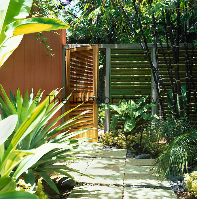 View of garden entrance surrounded by tropical planting with rendered wall and green syained wooden louvre walls and door