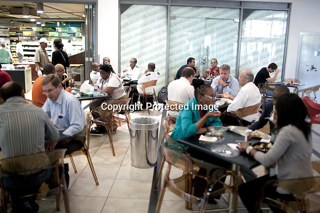 CAPE TOWN, SOUTH AFRICA - MARCH 20: Unidentified officers workers in a resataurant on March 20, 2012 in Cape Town, South Africa. Most racial groups sit side by side and don't mix. (Photo by Per-Anders Pettersson)
